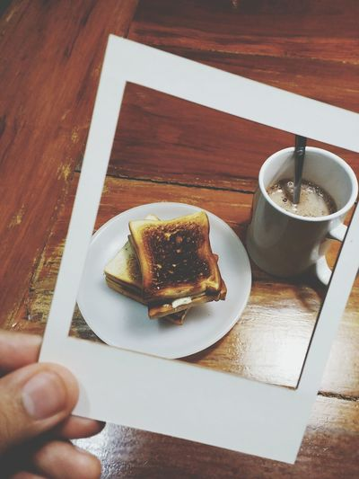 Cropped Image Of Hand Holding Breakfast Photograph Against Wooden Table