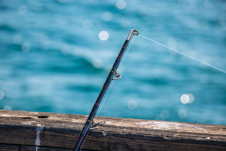 Close-up of fishing rod on wood against sea
