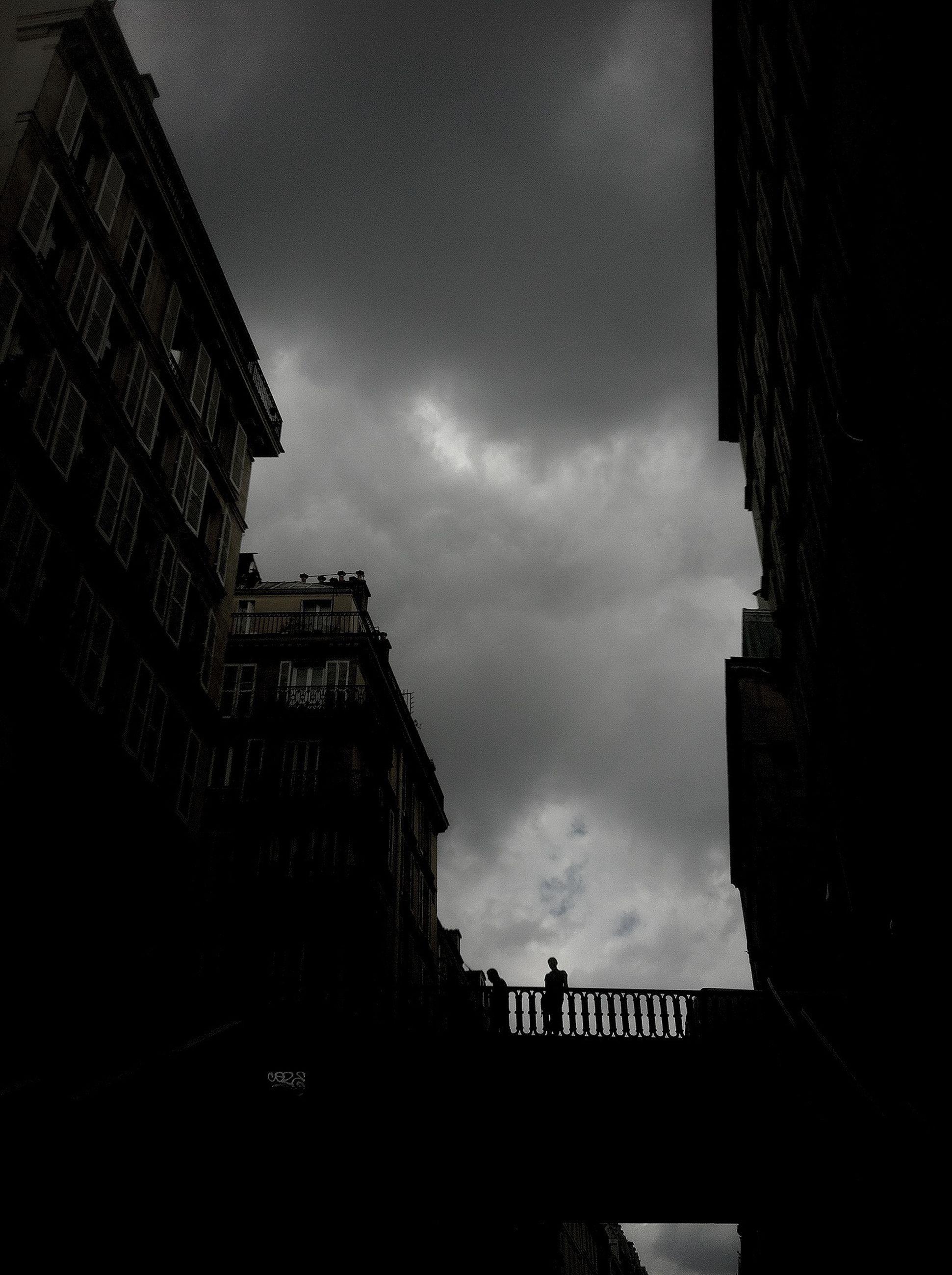 architecture, built structure, building exterior, sky, low angle view, building, cloud - sky, city, silhouette, cloudy, cloud, residential building, railing, outdoors, day, city life, dusk, residential structure