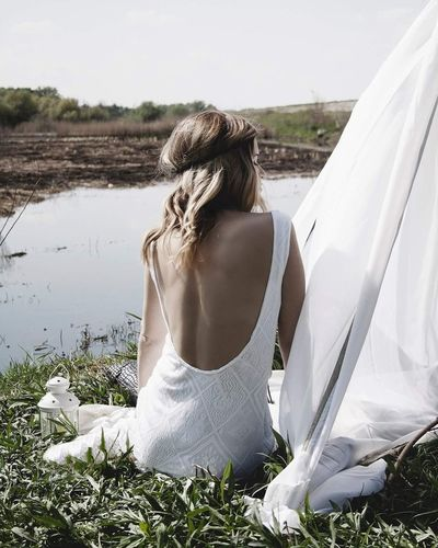 Rear view of young woman wearing backless dress while sitting at lakeshore
