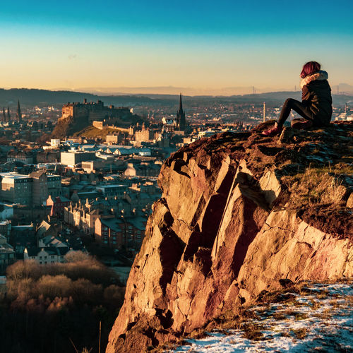 Woman sitting on rock against cityscape