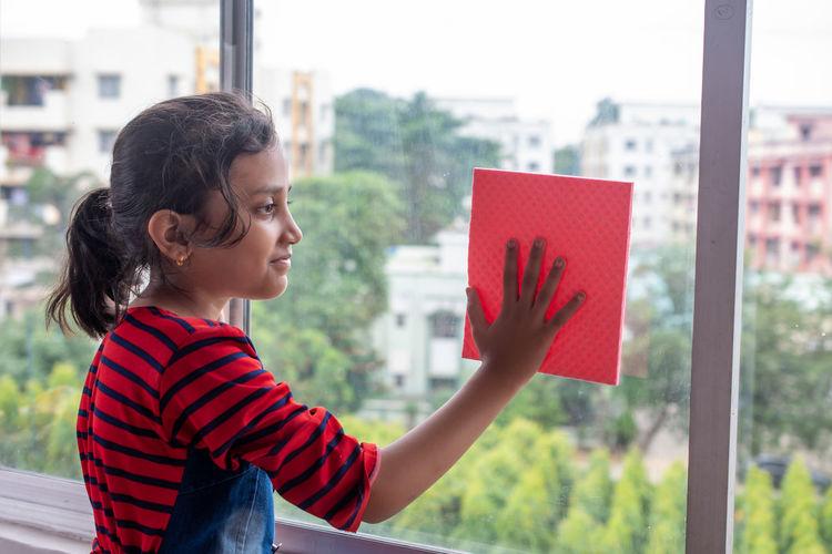 Side view portrait of smiling girl standing indoor