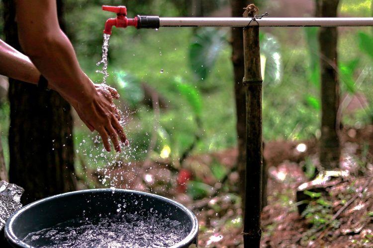 Person washing hands under running water