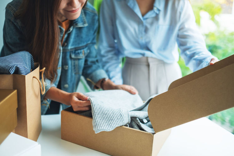 Midsection of woman holding paper in box
