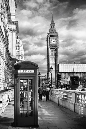 Telephone booth on sidewalk with big ben against sky