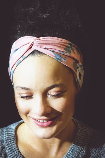 Smiling young woman wearing bandana against black background