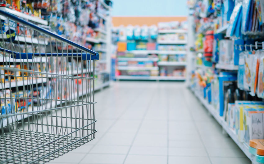 Conceptual image of shopping cart over blurry shelve of goods