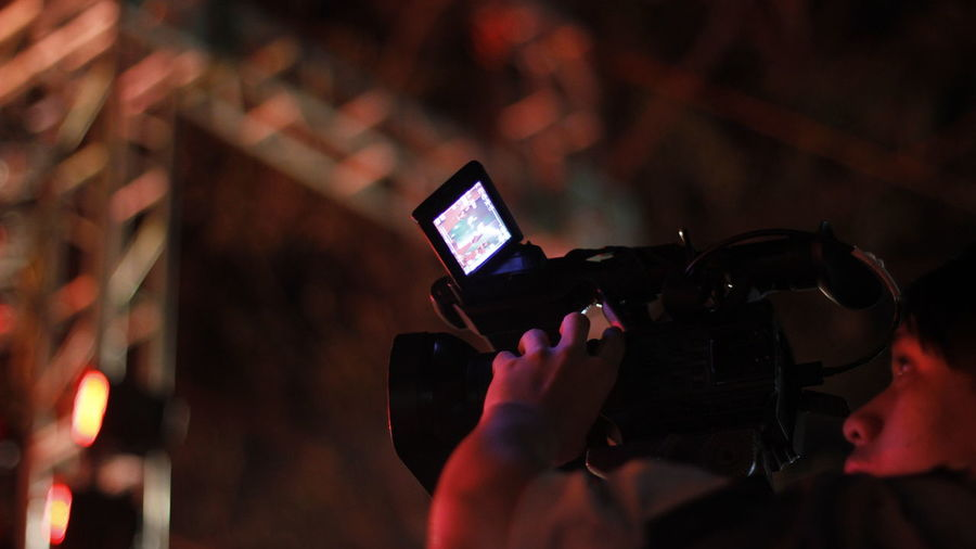 Low angle view of man filming with movie camera at night