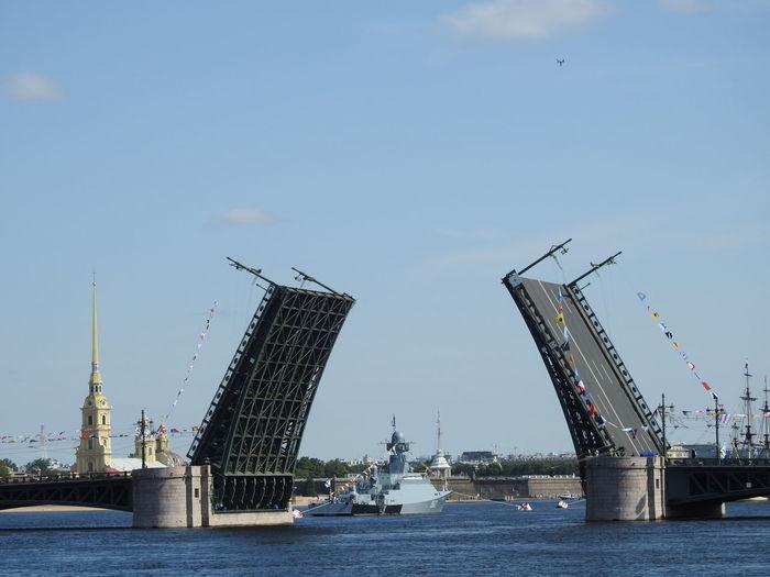 Bridge by river against sky in city