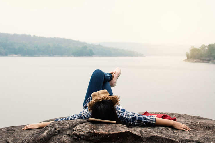 Young woman lying on rock by lake against clear sky