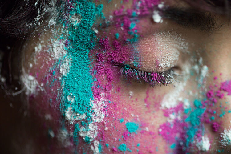 Woman with multi colored paints on face