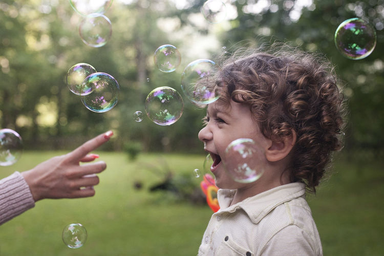 Boyhood Bubbles Fun Blowing Boy Bubble Bubble Wand Child Childhood Focus On Foreground Fragility Hand Headshot Joy Joyfull Leisure Activity Lifestyles Lightweight Men Nature Outdoors Real People Soap Sud Transparent Vulnerability  The Photojournalist - 2018 EyeEm Awards The Portraitist - 2018 EyeEm Awards A New Beginning Holiday Moments A New Perspective On Life Human Connection Moments Of Happiness