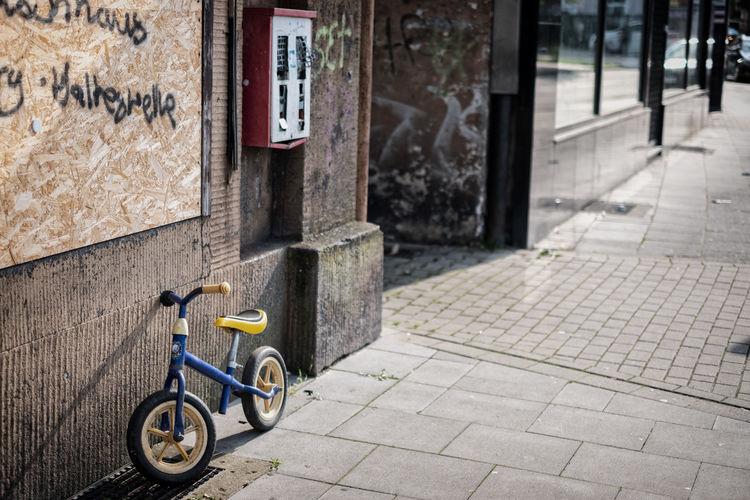 Bicycle on footpath against building