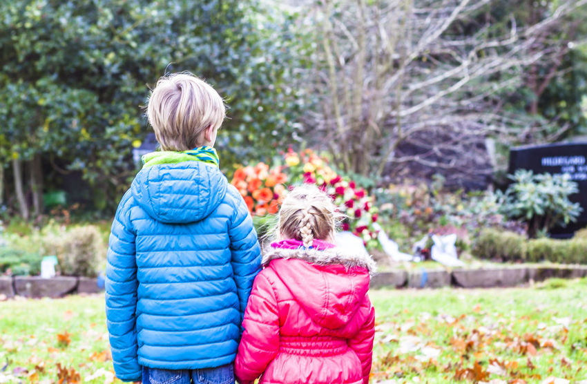 Little brother and sister standing at the grave of their parents in the graveyard Children Death Grave Memorial Mourning Accident Boy Calamity Cemetry Child Childhood Crying Crying Child Doughter  Emotional Funeral Girl Graveyard Honor Kid Orphan Parents Plant Sibling Son