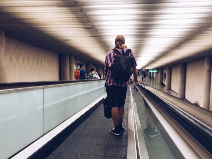 Rear View Of Man On Moving Walkway