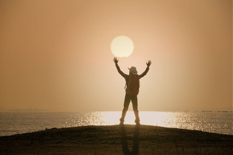 Man standing and open hand on sunset or sunrise background Man Standing Open Hand Sun Sunset Sunrise Sunlight Backpack Happy