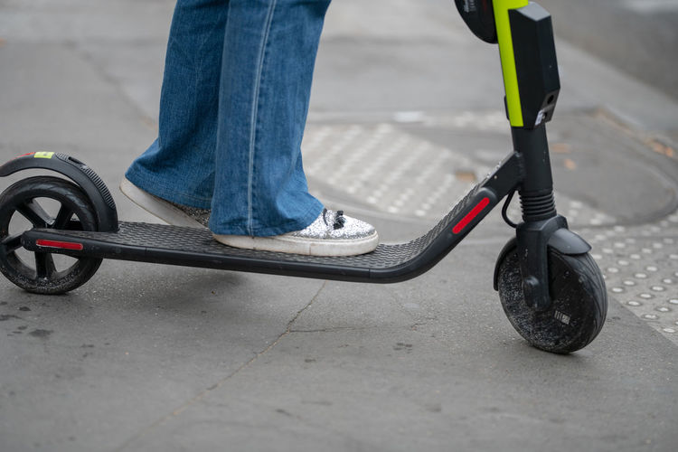 Low section of person on push scooter on street