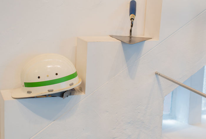 Trowel and white construction helmet on a wall Construction Construction Site Craftsman Modernized Trowel Wall Working Brick Bricklayer Build Building Construction Helmet Construction Worker Craft Expand Hand Tool House Modernize Equipment And Appliances Occupation Stone Tool
