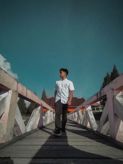 Full length of young man standing on bridge against sky