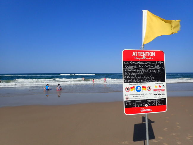 Attention! Caution Sign Signage Notice Yellow Flag Flags In The Wind  Flag Gold Coast Gold Coast Australia Surfers Paradise Summer Beach Sea Red Water Lifeguard  Horizon Over Water Vacations Safety Outdoors Travel Destinations Swimming Blue Sand Nature Wave Lifeguard Hut Communication Clear Sky Scenics Real People Summer Road Tripping