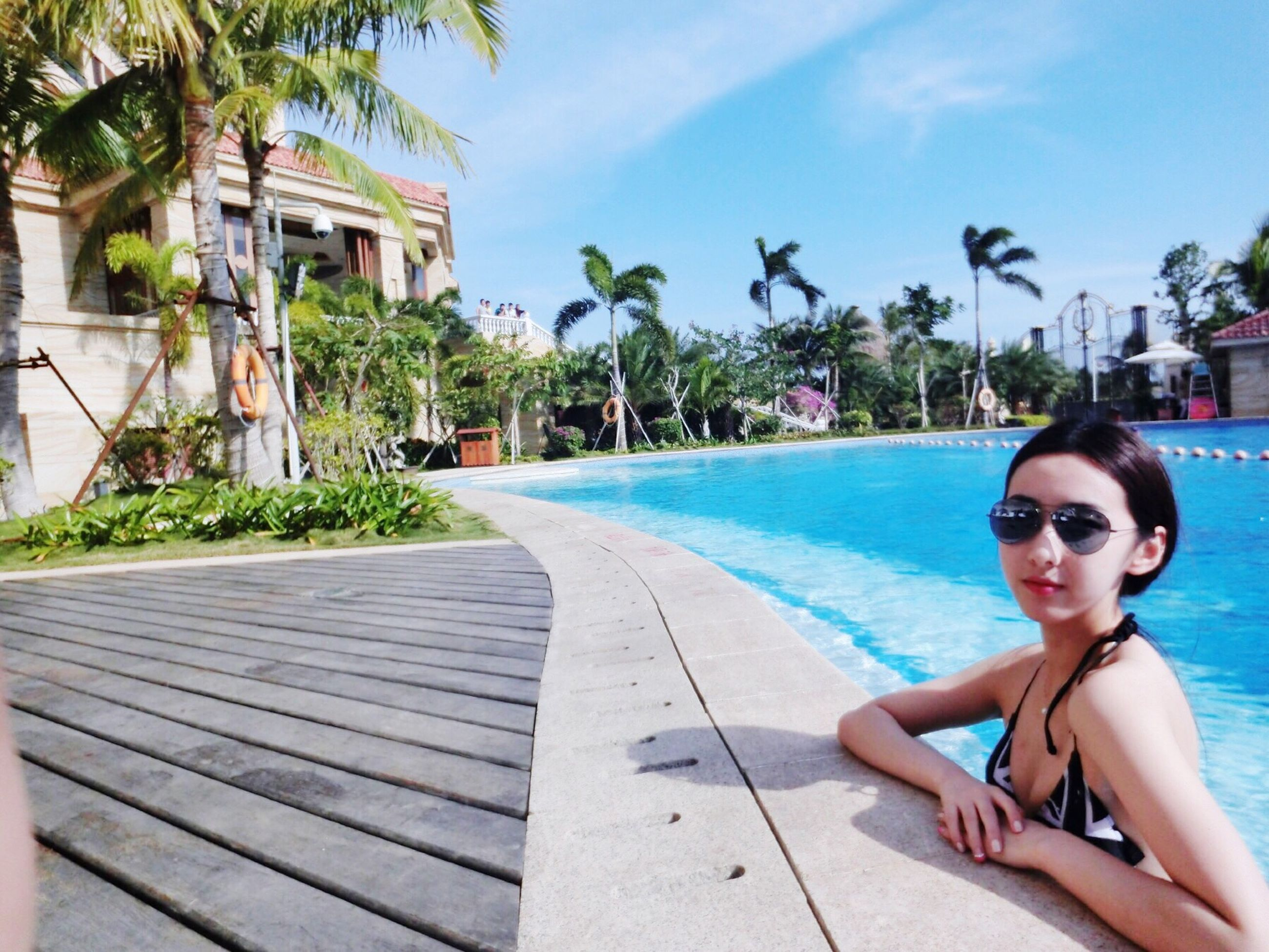 lifestyles, leisure activity, beach, person, palm tree, sea, sky, sunlight, water, swimming pool, young adult, blue, tree, young women, day, childhood, outdoors, sunglasses