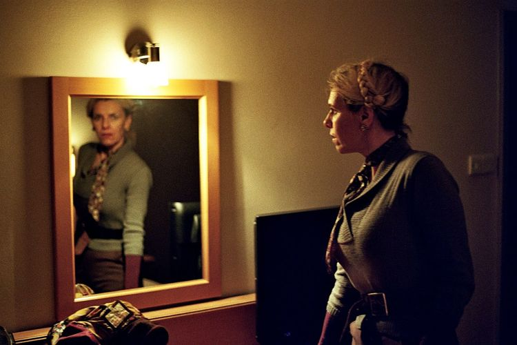 Woman standing in front of mirror at home