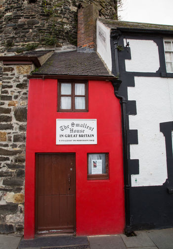 The smallest house in Great Britain in Conwy North Wales Architecture Built Structure Building Exterior Red Building Text Entrance Day Communication Door Wall Wall - Building Feature No People Western Script Outdoors Sign House Safety Information Number Brick Conwy Smallest House In Great Britain Smallest House In Conwy