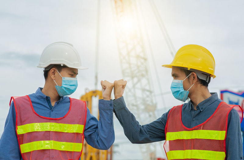 Young man wearing hat standing at construction site