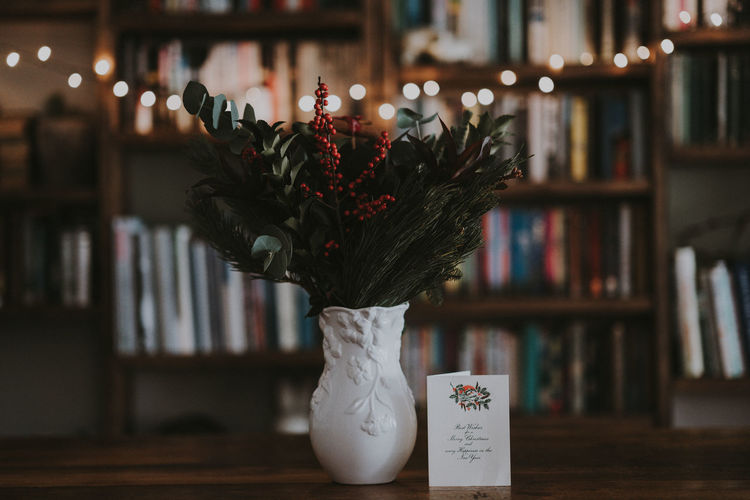 Flower vase with greeting card on table