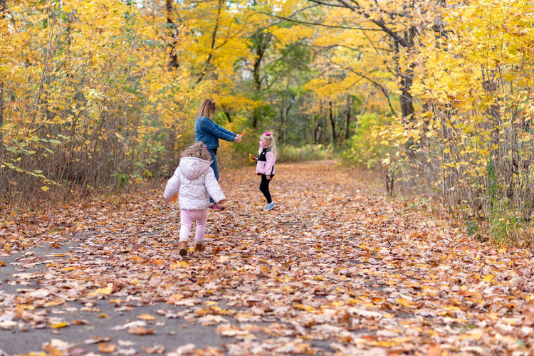 Full length of mother playing with daughters in forest during autumn