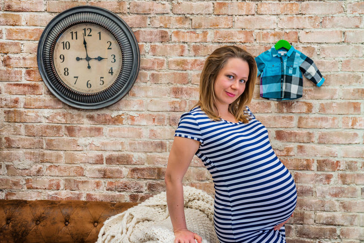 Portrait of smiling pregnant woman standing against brick wall