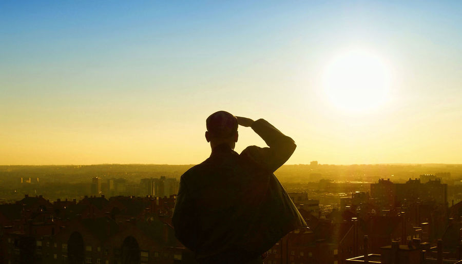 Rear view of man shielding eyes against sky during sunset