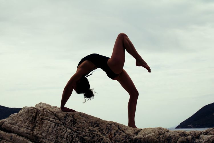 Rear view of woman in swimsuit doing yoga on rock by sea against sky