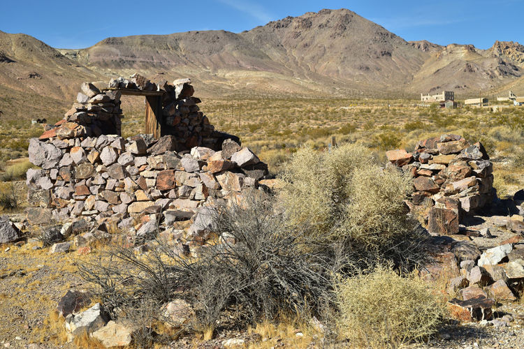 Deteriorating walls abandoned stone house in mojave desert with one window frame with mountain view