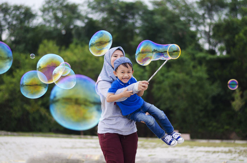 Mother and son making bubbles with wand against trees