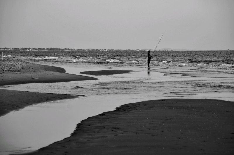 Man fishing on beach against sky