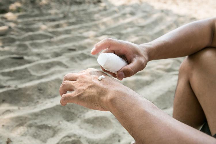 Close-up of man applying moisturizer on hand