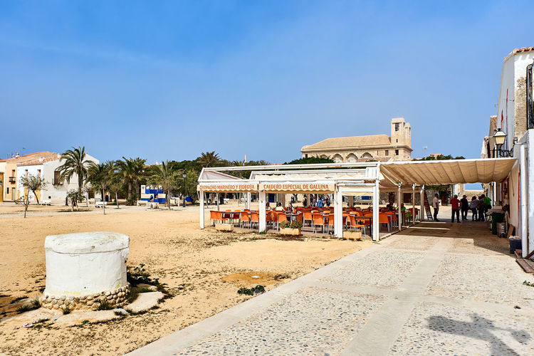 Island of Tabarca, Spain - March 11, 2017: Outdoors cafe in the waterfront street in the Island of Tabarca. Spain Footpath Holiday SPAIN Seashore Sidewalk Tabarca's Island Beach Cafe Clear Sky Day Europe Landscape Open Air Cafe Open Air Restaurant Outdoors Scenery Seafront Sidewalk Cafe Street Sunny Day Tabarca Tourist Resort Town Travel Destinations