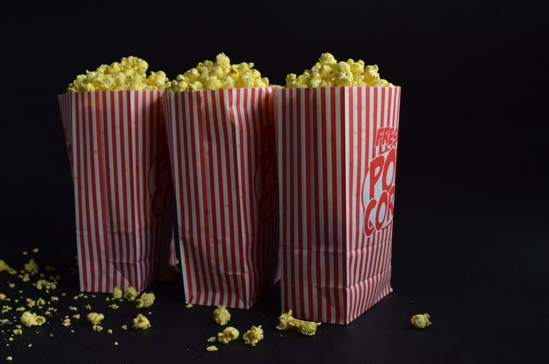 three red and white striped bags of buttered popcorn Abundance Arrangement Black Background Buttered Popcorn Choice Close-up Colorful Group Of Objects In A Row Multi Colored No People Popcorn Repetition Side By Side Snack Snack Time Still Life Studio Shot Variation