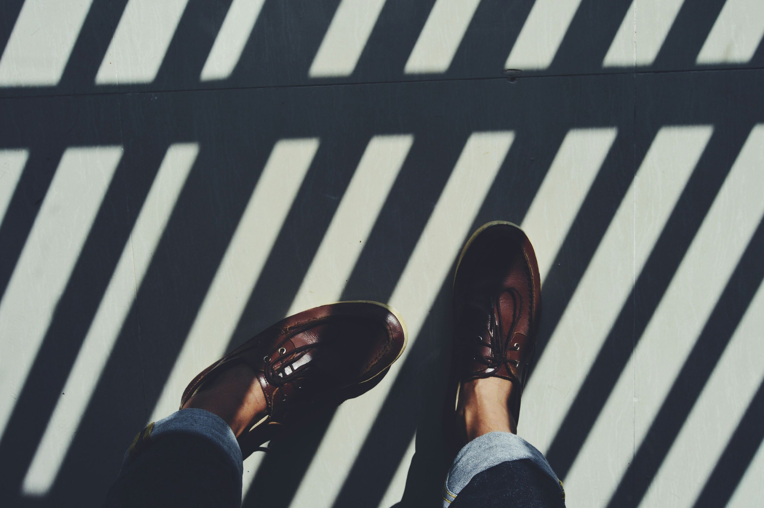 low section, person, lifestyles, personal perspective, shoe, standing, leisure activity, high angle view, human foot, men, footwear, shadow, day, street, jeans, sunlight