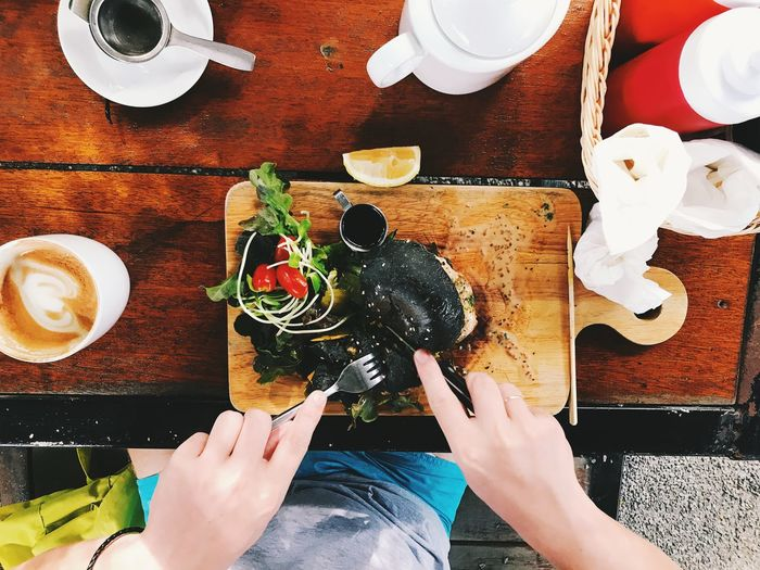 High angle view of hand holding black burger on table