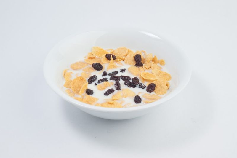 Bowl of milk with corn flakes and raisins