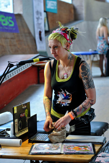 Riga,Latvia- July 13,2013:First Baltic Tattoo Convention in VEF Skatepark,working tattoo masters, tattoo art close up,tattooed young people and spectators Adult Adults Only Artist Blond Hair Body Arts Candid Portraits Casual Clothing Day Front View Headband Holding Indoors  One Person People Piercing Piercing :) Real People Skill  Small Business Standing Tattoo Work Tattoos Technology Workshop Young Adult
