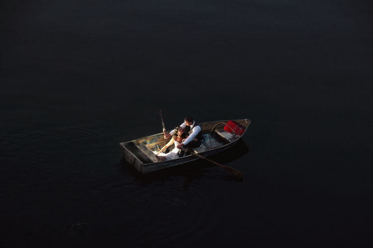 High angle view of people on boat against black background