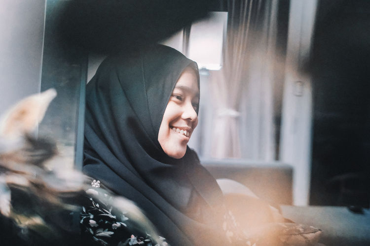 One Person Real People Lifestyles Indoors  Smiling Happiness Front View Sitting Young Adult Leisure Activity Casual Clothing Portrait Emotion Headshot Home Interior Young Women Looking Women Selective Focus Hairstyle Beautiful Woman Woman In Hijab