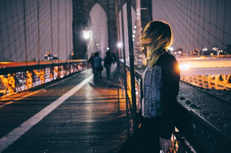 Woman walking on railroad station platform at night