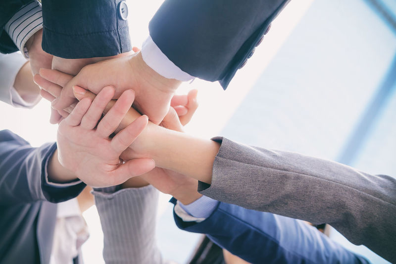 Cropped image of business people stacking hands at office