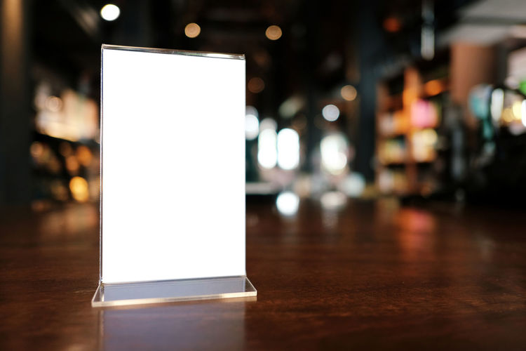 Advertisement Bar Counter Billboard Blank Business Commercial Sign Communication Copy Space Empty Flooring Focus On Foreground Illuminated Indoors  Light Lighting Equipment Marketing Message Night No People Paper Reflection Sign Table White Color Wood - Material