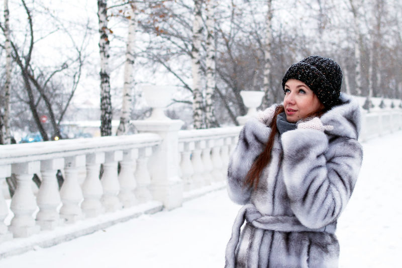 Full length of woman standing by railing during winter