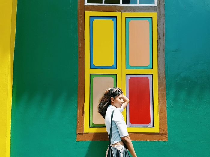 Side view of woman with hand in hair standing by colorful window